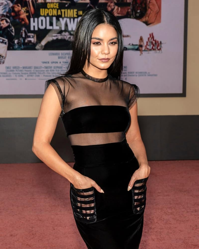 On July 22, 2019, Vanessa Hudgens wore a very fashionable black dress with long and straight black hairstyle with subtle layers at The Los Angeles Premiere Of