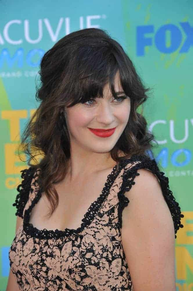Zooey Deschanel was at the 2011 Teen Choice Awards at the Gibson Amphitheatre, Universal Studios, Hollywood on August 7, 2011, in Los Angeles, CA. She wore a floral dress to pair with her long and tousled wavy dark half-up hairstyle with bangs.