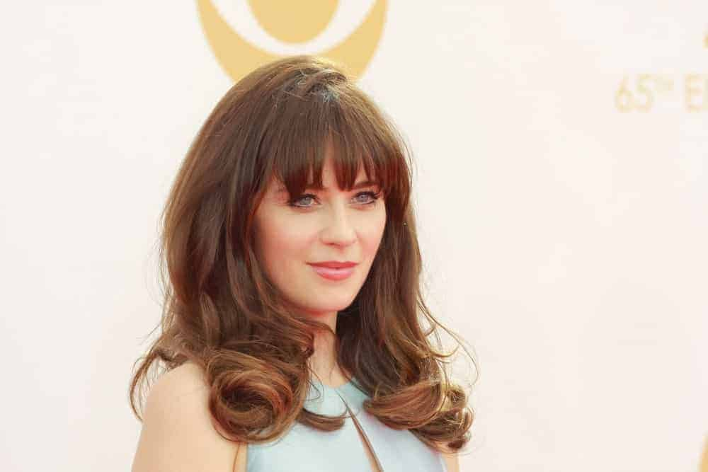 Zooey Deschanel was at the 65th Primetime Emmy Awards at the Nokia Theatre, LA Live on September 22, 2013, in Los Angeles, CA. She paired her gray dress with a tousled brunette hairstyle that is loose on her shoulders with large curls.