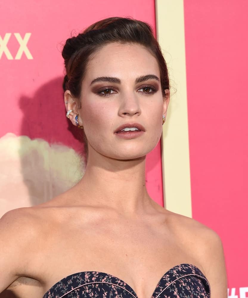 Lily James tied and twisted her natural brunette locks in a low ponytail as she arrives for the