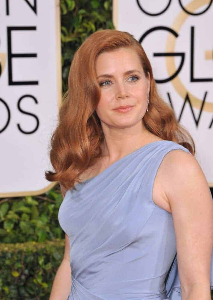 On January 11, 2015, Amy Adams attended the 72nd Annual Golden Globe Awards at the Beverly Hilton Hotel, Beverly Hills. She paired her gray dress with her side-swept wavy red hairstyle with a slight tousle.