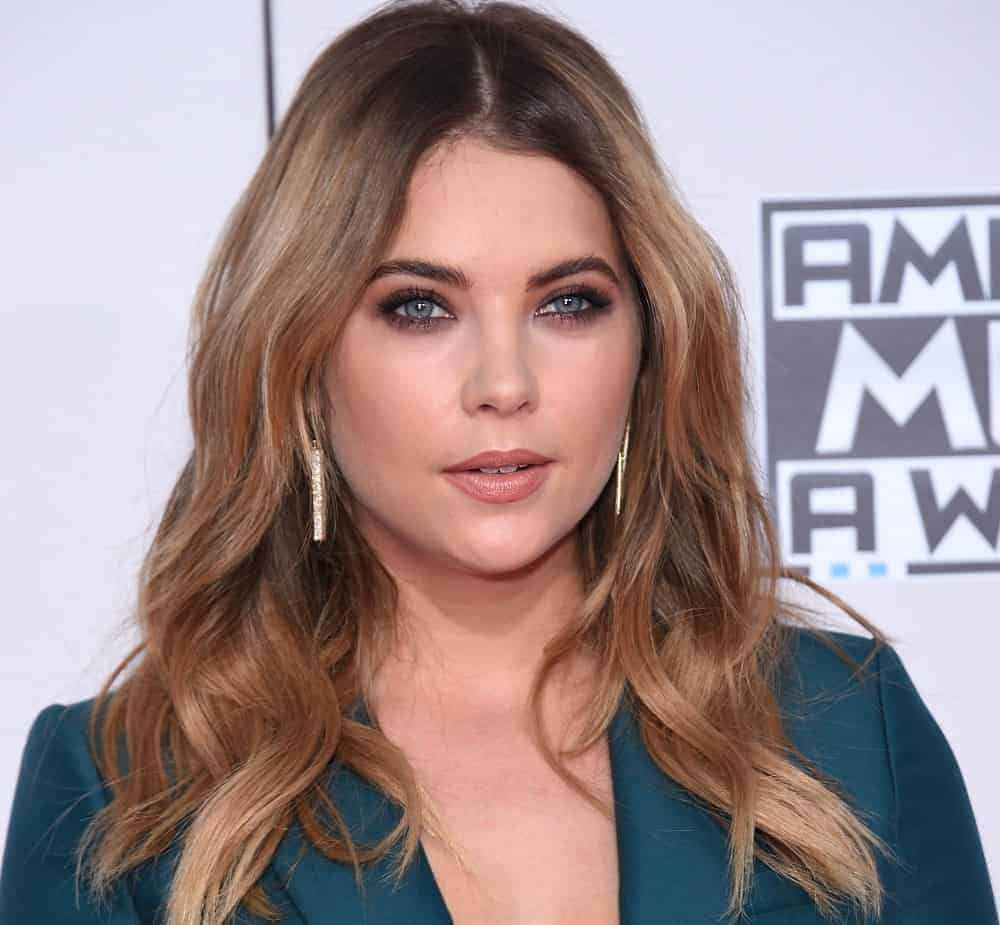 Ashley Benson attended the American Music Awards 2015 on November 22, 2015, in Los Angeles, CA. She was lovely in her dark green pantsuit and long, layered wavy sandy blonde hairstyle with a loose and tousled finish.