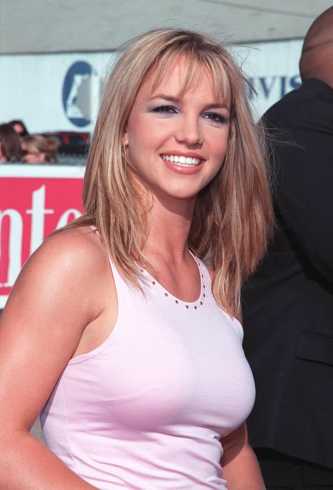 Britney Spears kept it casual with a pink sleeveless top paired with her tousled mid-length hair incorporated with airy bangs. This was taken at the 1999 Teen Choice Awards in Santa Monica, where she won for Single of the Year for
