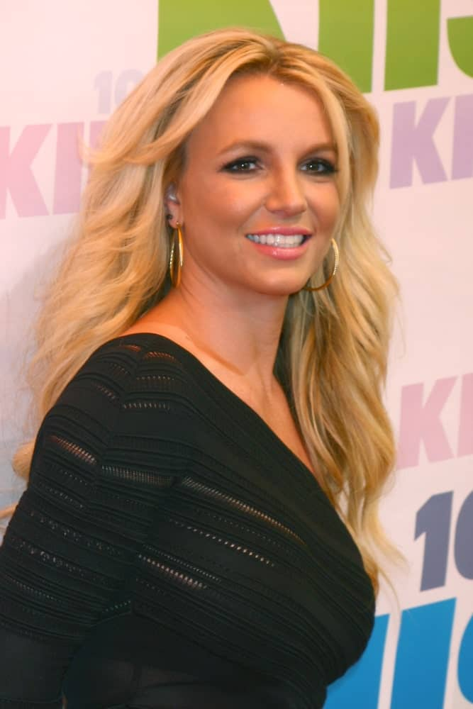 Britney Spears contrasted her blonde wavy hair with a one-shoulder black dress that was worn at the 2013 Wango Tango concert produced by KIIS-FM on May 11, 2013.