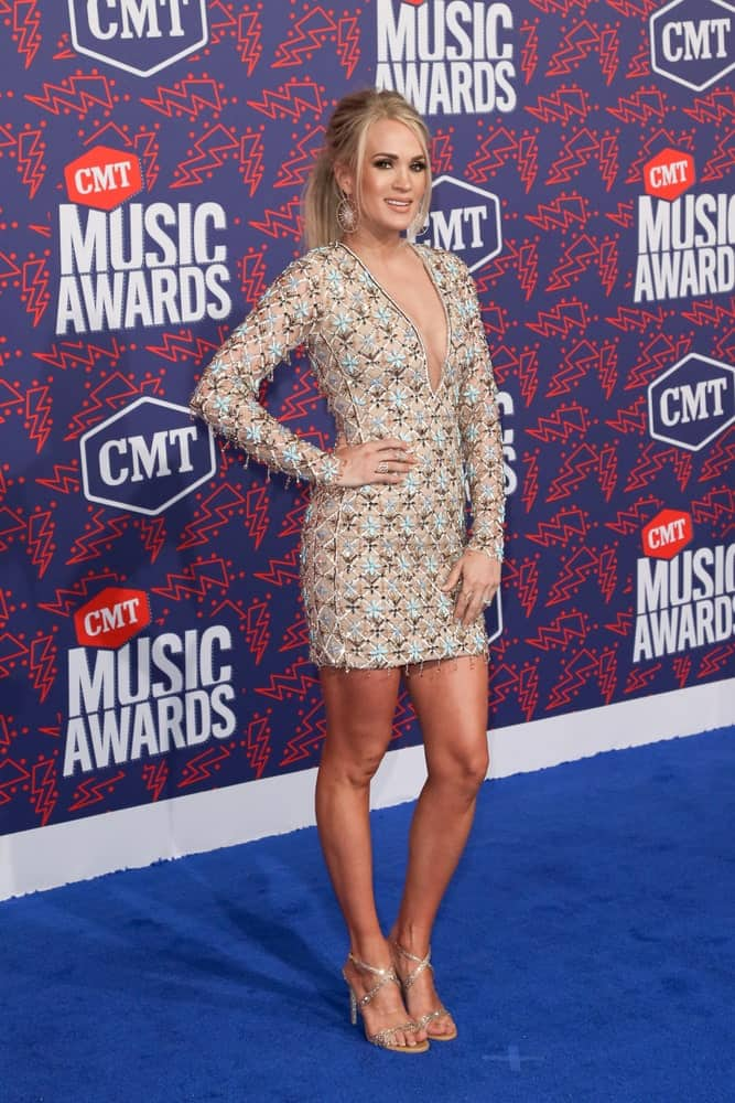 Carrie Underwood with her plunging V neckline dress and a ponytail with loose tendrils as she attends the 2019 CMT Music Awards at the Bridgestone Arena on June 5, 2019.