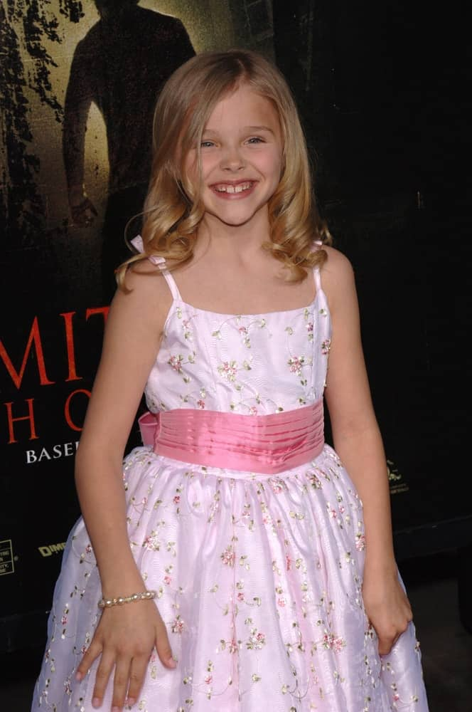 Young actress Chloe Grace Moretz was at the world premiere of her new movie The Amityville Horror on April 7, 2005. She wore a white floral dress with her sandy blonde hairstyle that has curls at the tips.