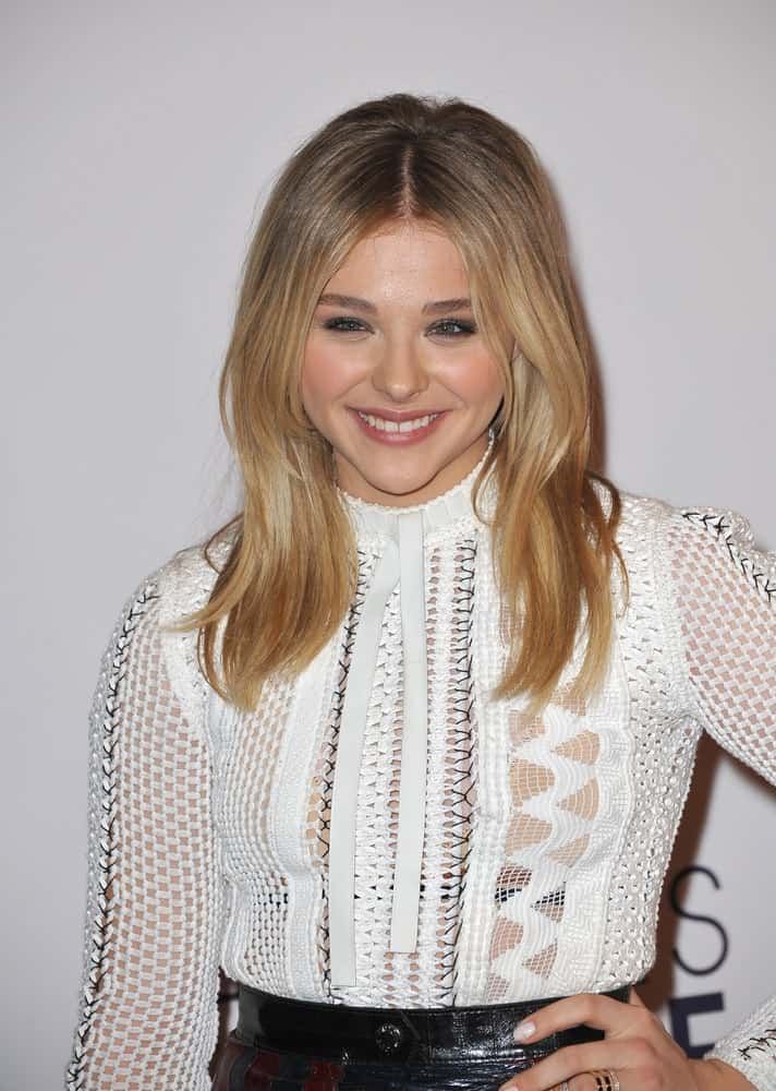 On January 7, 2015, Chloe Grace Moretz attended the 2015 People's Choice Awards at the Nokia Theatre L.A. Live downtown Los Angeles. She wore a lovely white blouse to pair with her long sandy blonde hairstyle with layers and highlights.