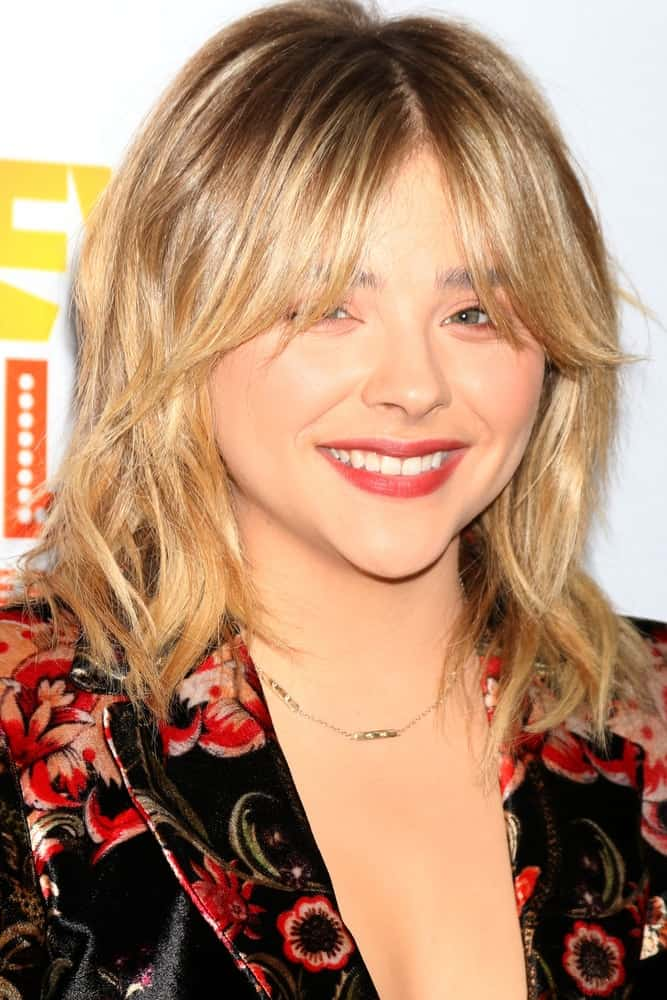 Chloe Grace Moretz was at the TrevorLIVE Los Angeles 2016 at Beverly Hilton Hotel on December 4, 2016 in Beverly Hills, CA. She wore a colorful floral smart casual outfit with her shaggy sandy blonde hairstyle with layers and eye skimmer bangs.