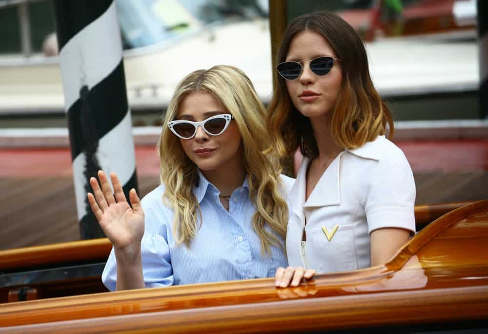 Chloe Grace Moretz and Mia Goth were seen waving at the fans during the 75th Venice Film Festival on September 1, 2018 in Venice, Italy. Moretz was wearing a casual outfit with a pair of cat-eye sunglasses and tousled wavy sandy blonde hairstyle.