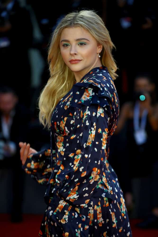 Chloe Grace Moretz walked the red carpet of the 'Suspiria' screening during the 75th Venice Film Festival on September 1, 2018 in Venice, Italy. She wore a lovely colorful dress that paired well with her long and tousled loose sandy blonde hairstyle that has layers.