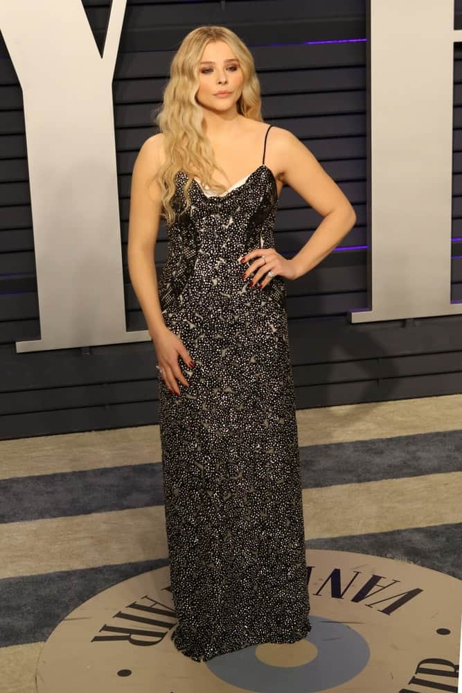 Chloe Grace Moretz was at the 2019 Vanity Fair Oscar Party on the Wallis Annenberg Center for the Performing Arts on February 24, 2019 in Beverly Hills. She paired her elegant bedazzled black dress with a long and tousled wavy blonde hairstyle that is loose on her shoulders.