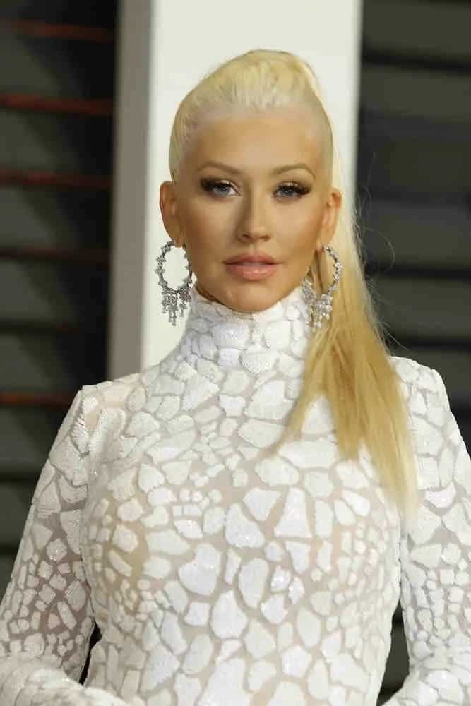 Christina Aguilera looks flawless in an all-white floor-length crack effects gown and her straightlong blonde hair was styled into high ponytail at the Vanity Fair Oscar Party 2015 on February 22, 2015.