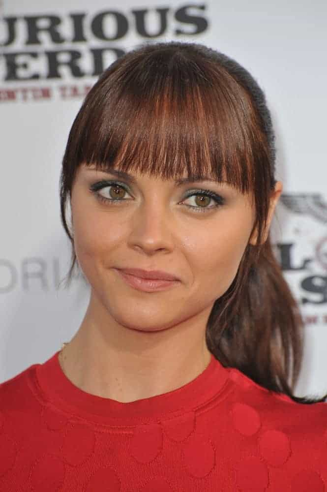"""On August 10, 2009, Christina Ricci attended the Los Angeles premiere of """"Inglourious Basterds"""" at the Grauman's Chinese Theatre, Hollywood. She wore a red dress that paired well with her highlighted brunette ponytail hairstyle with blunt bangs."""