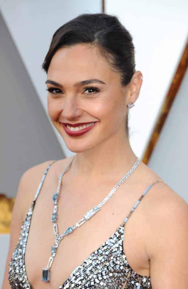 Gal Gadot attended the 90th Annual Academy Awards held at the Dolby Theatre in Hollywood, USA on March 4, 2018. She wore a matching necklace for her silver sequined dress and a slick side-swept ponytail hairstyle.