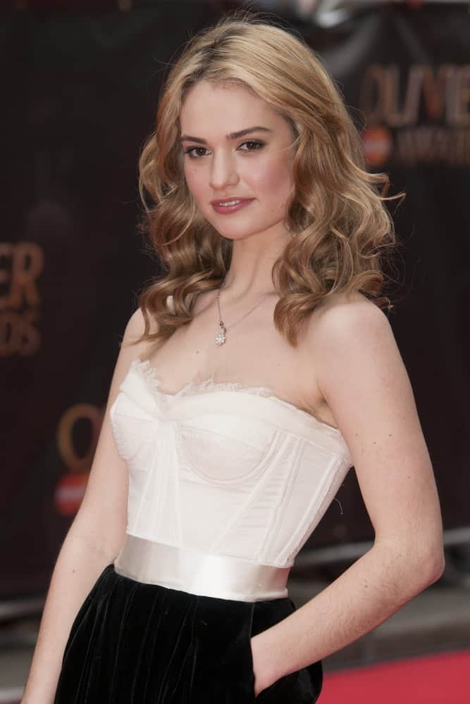 Lily James attended the Laurence Olivier Awards 2013 at the Royal Opera House, Covent Garden, London on April 28, 2013. She was sexy in a bustier dress that she paired with her shoulder-length curly sandy blonde hairstyle with layers and subtle highlights.