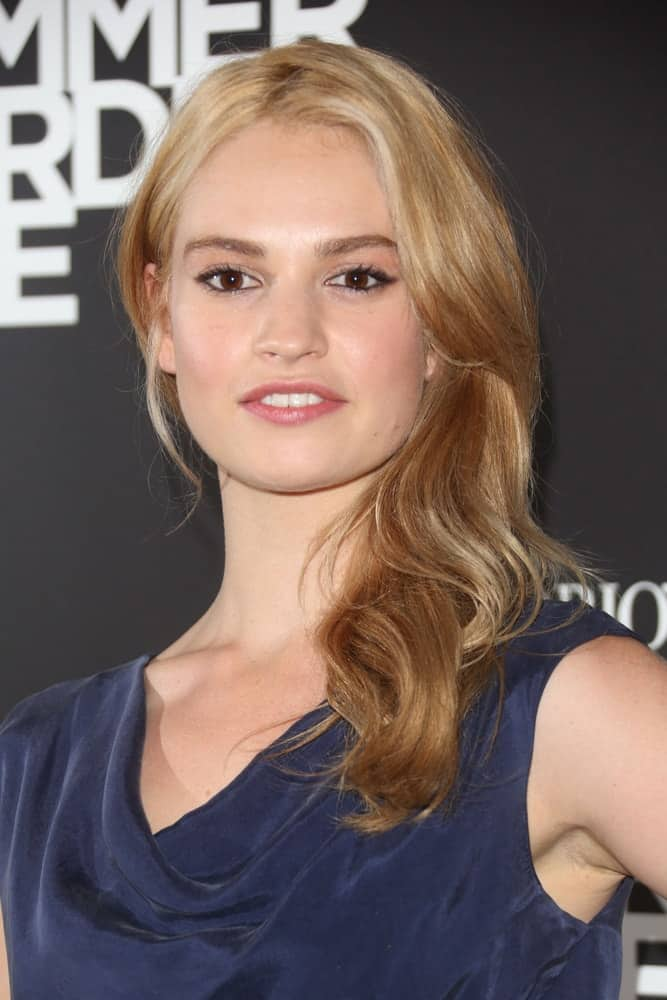 Lily James was at the Emporio Armani Summer Garden Live 2013, London on July 16, 2013. She was seen wearing a charming blue dress to pair with her medium-length side-swept ombre sandy blonde hairstyle with waves and layers.