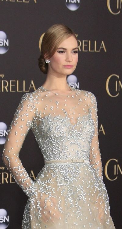 """Lily James was at the """"Cinderella"""" World Premiere at the El Capitan Theater on March 1, 2015 in Los Angeles, CA. She wore an elegant and stunning gown that paired perfectly with her sandy blonde low bun hairstyle with a slick finish."""