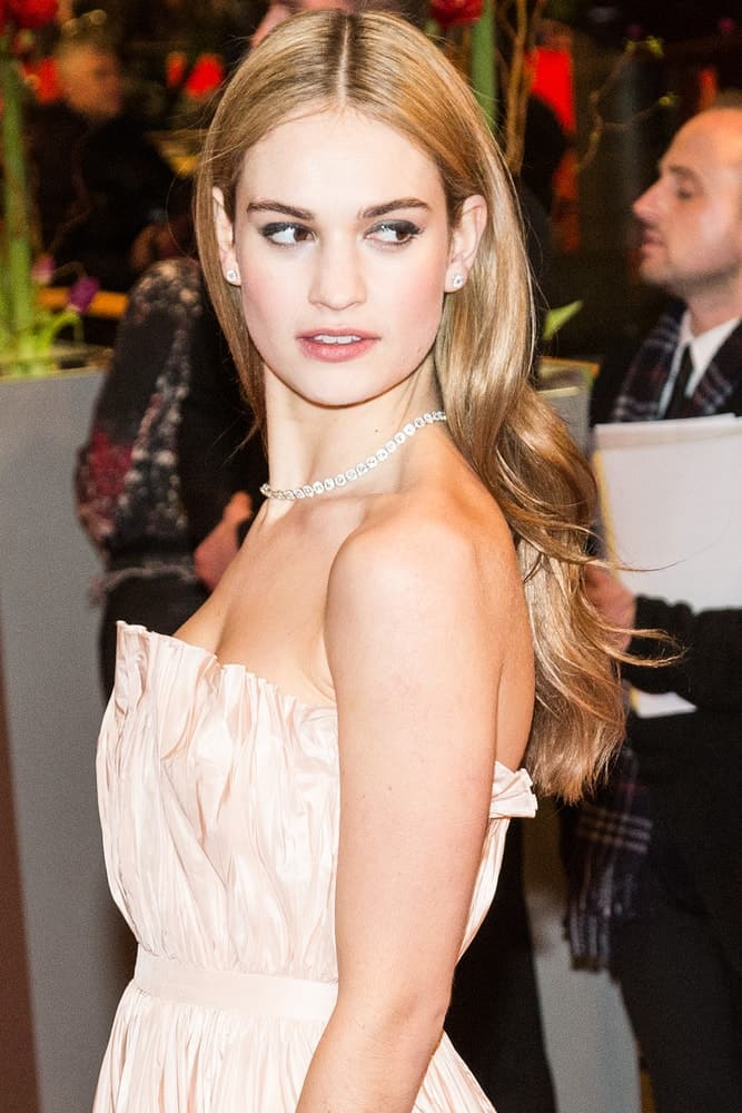 Lily James attended the 'Cinderella' premiere during the 65th Berlinale Film Festival at Berlinale Palace on February 13, 2015 in Berlin, Germany. She wore a charming strapless dress to pair with her long and wavy sandy blonde hairstyle loose and tousled on her back.