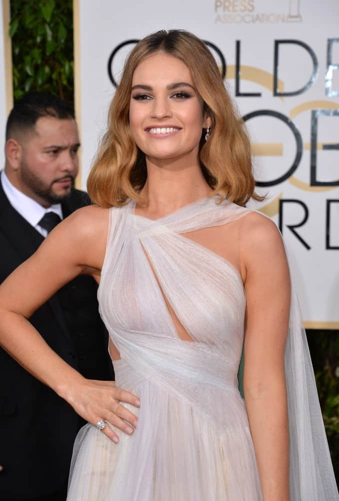 On January 10, 2016, Lily James was at the 73rd Annual Golden Globe Awards at the Beverly Hilton Hotel. She wore a stunning white dress that she paired with a wavy sandy blonde shoulder-length bob hairstyle with subtle highlights.