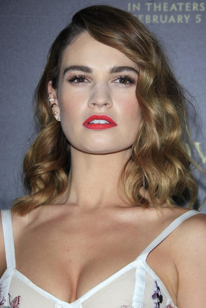 Lily James was at the Pride And Prejudice And Zombies Premiere at the Harmony Gold Theatre on January 21, 2016 in Los Angeles, CA. She was charming in a white dress that she paired with red lips and curly brunette shoulder-length hairstyle with side-swept bangs.