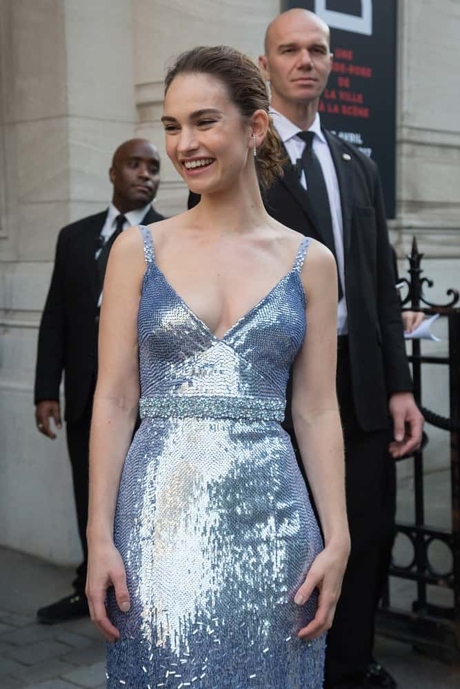 Lily James attended the Vogue Foundation Dinner as part of Paris Fashion Week Haute Couture Fall/Winter 2017-2018 in Paris, France. She wore a lovely silver dress that she paired with a brunette bun hairstyle with a slick finish.