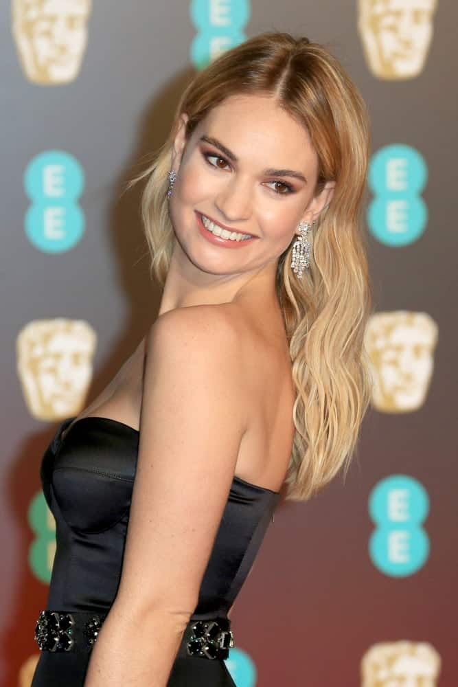 On February 18, 2018, Lily James attended the EE British Academy Film Awards (BAFTAs) held at the Royal Albert Hall in London, UK. She was quite charming in a black dress with her long and wavy sandy blonde hairstyle with layers and highlights.