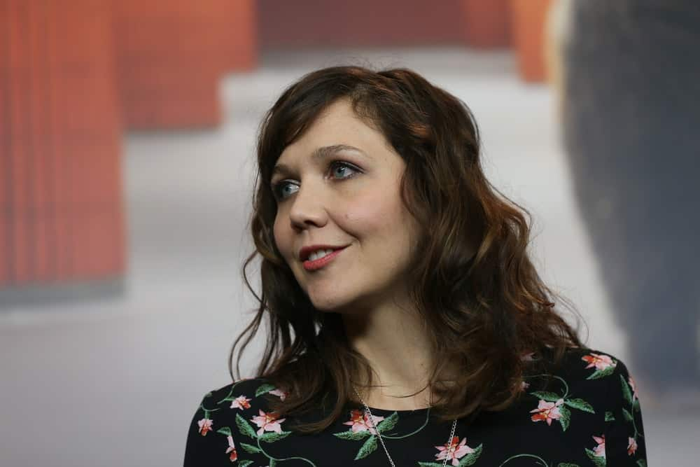 Maggie Gyllenhaal attended the International Jury press conference during the 67th Berlinale International Film Festival Berlin at Grand Hyatt Hotel on February 9, 2017 in Berlin, Germany. She wore a black floral dress with her medium-length curly and highlighted hairstyle that is loose and tousled.