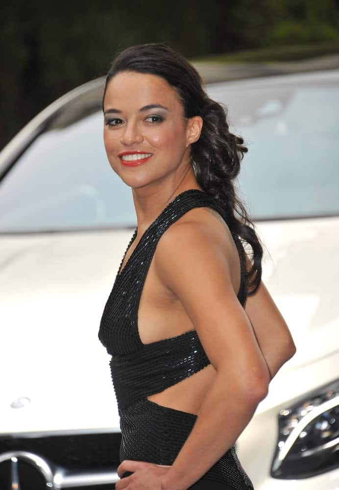Michelle Rodriguez strikes a pose flaunting her long black waves in ponytail hairstyle during the 21st annual amfAR Cinema Against AIDS Gala on May 22, 2014.