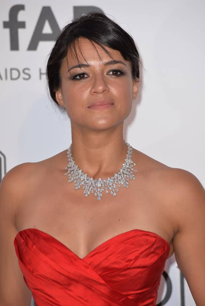 Michelle Rodriguez looks ravishing in a red tube dress and a loose upstyle with thin, scattered bangs during the 2015 amfAR Cinema Against AIDS gala on May 21, 2015.