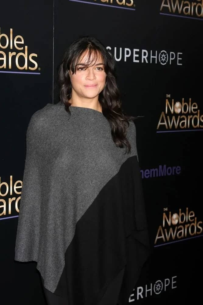 Michelle Rodriguez went fancy in a black and gray knit poncho paired with a baggy black jumper. She matched this comfy look with pretty loose curls with a spot of fringe as she attends the Noble Awards on February 27, 2015.