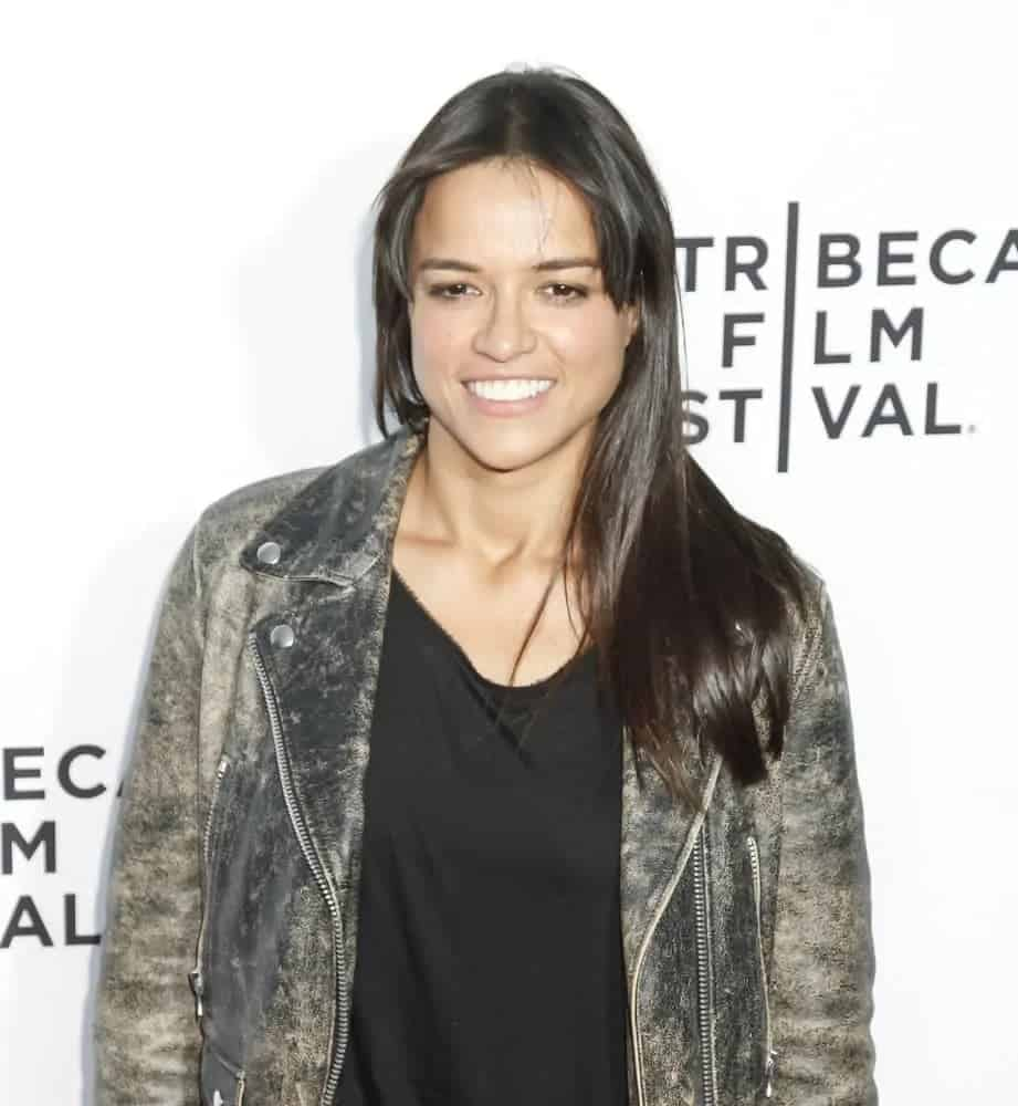 Michelle Rodriguez dresses down in a leather jacket and wore her sleek medium-length hairin loose straight, rested in one shoulder with middle-part bangs at the world premiere of Live From New York on April 15, 2015.