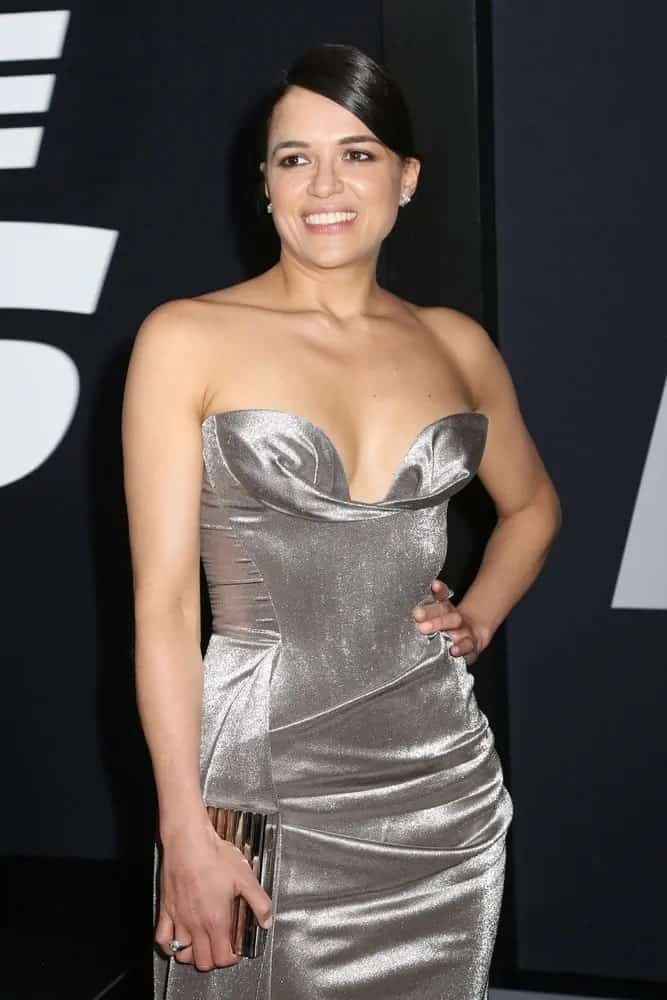 Michelle Rodriguez shimmers in a silver steel strapless gown and sensually pulled back her sleek side-part hair into a classic ponytail braid as she attends the premiere of