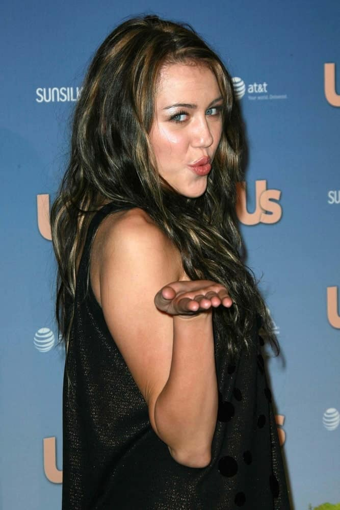 On September 26, 2007, Miley Cyrus wore a lovely black dress with her long and loose wavy hairstyle with layers and highlights at the US Weekly's Hot Hollywood 2007 Party in Hollywood, CA.