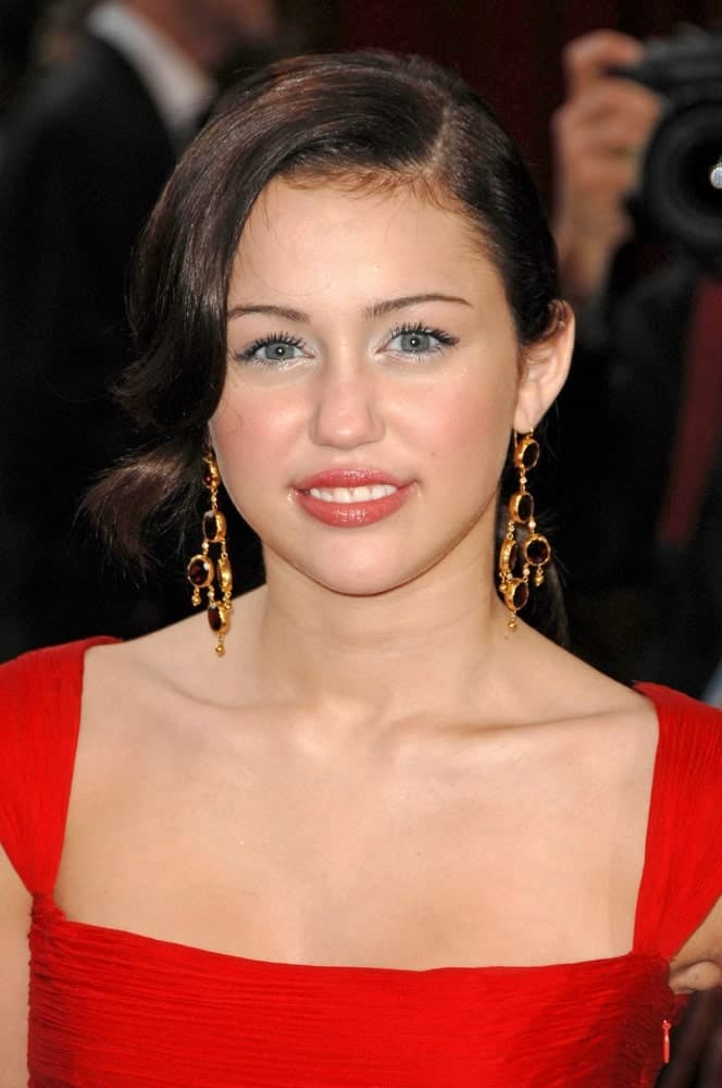 Miley Cyrus walked the red carpet of the 80th Annual Academy Awards Oscars Ceremony held at The Kodak Theatre in Los Angeles on February 24, 2008. She wore a gorgeous red dress that complemented her vintage side-swept waves.