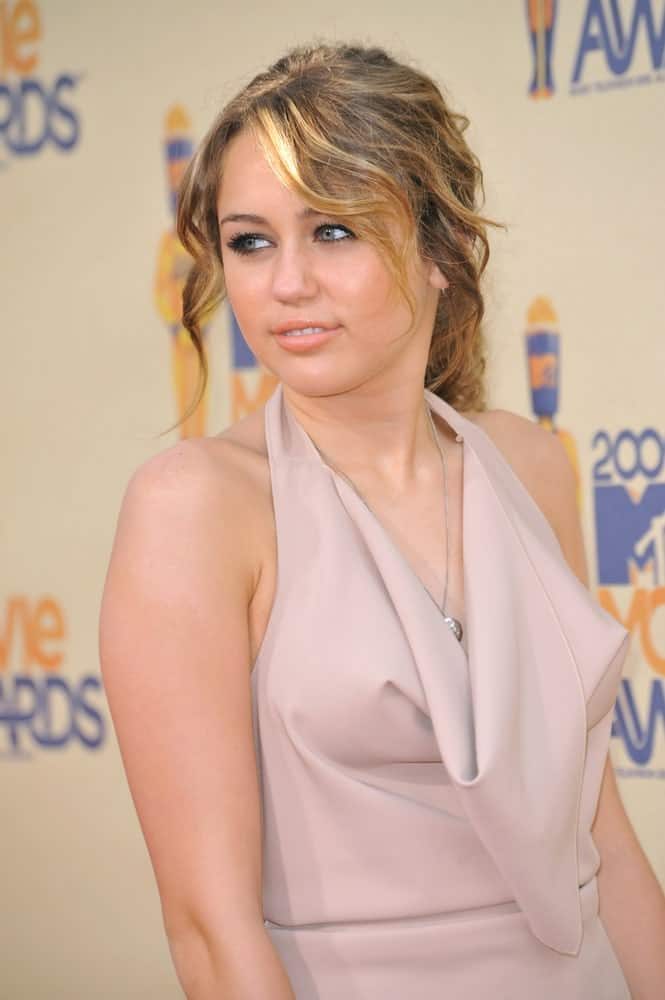 Miley Cyrus wore a lovely champagne dress that complemented her messy half-up curly highlighted hairstyle at the 2009 MTV Movie Awards at Universal Studios, Hollywood on May 31, 2009 Los Angeles, CA.