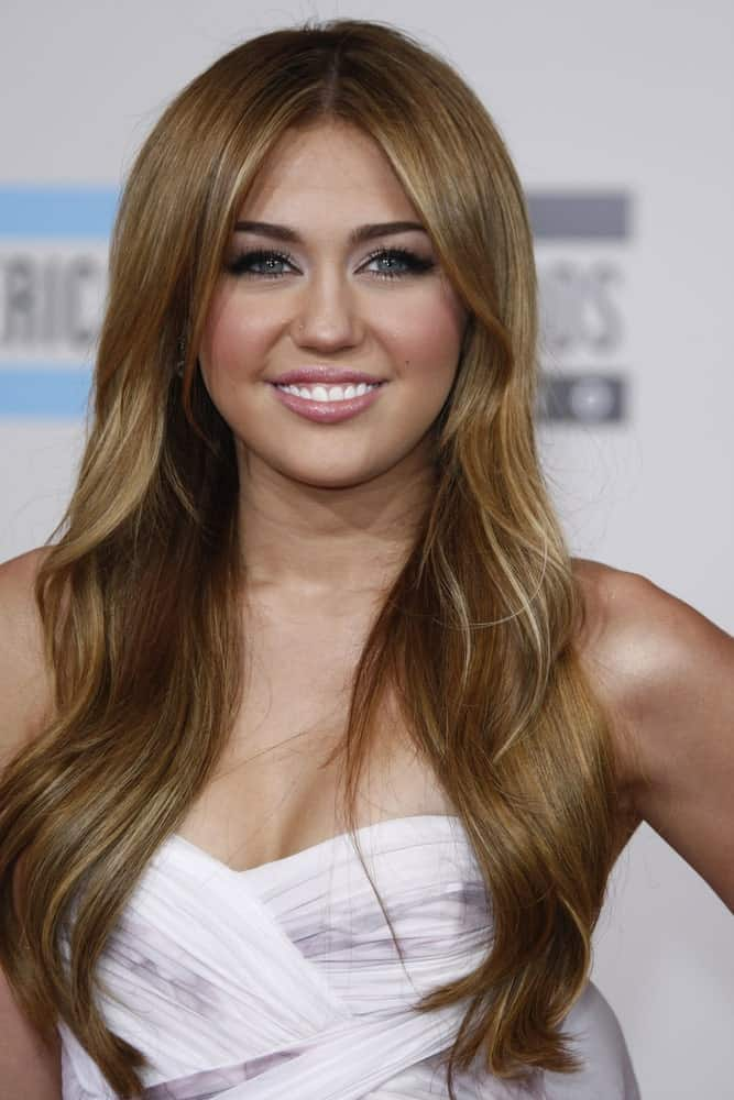 Miley Cyrus emphasized her gorgeous long layered wavy highlighted hairstyle with a lovely white dress at the 2010 American Music Awards held at the Nokia Theater in Los Angeles, California on November 21, 2010.