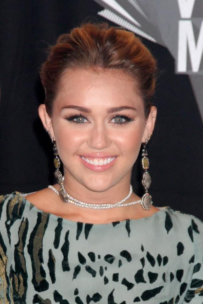 Miley Cyrus wore an animal print gray dress that she paired with a messy bun hairstyle to emphasize her lovely eyes and earrings at the 2011 MTV Video Music Awards at the LA Live on August 28, 2011 in Los Angeles, CA.