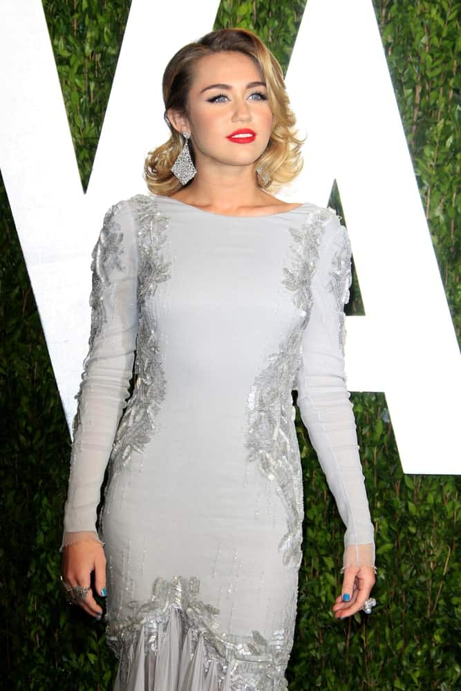 Miley Cyrus went for a classy vintage look for her medium length side-swept wavy hairstyle with elegant curls on the sides at the 2012 Vanity Fair Oscar Party at the Sunset Tower on February 26, 2012 in West Hollywood, CA.