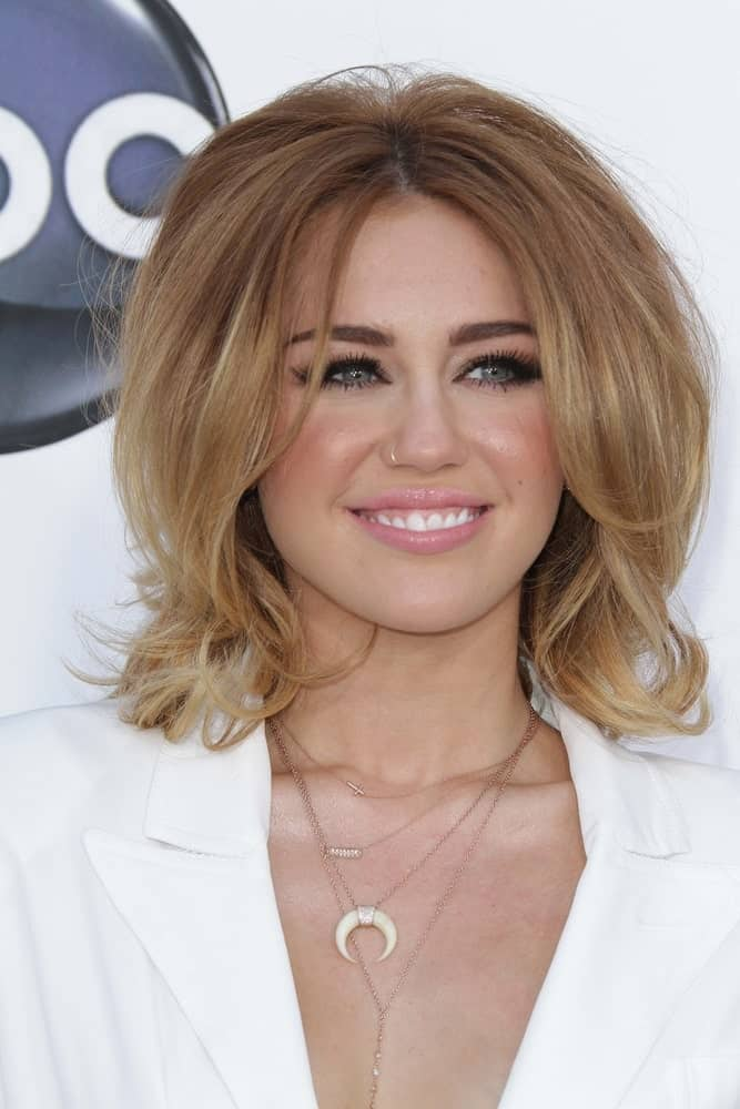 On May 20, 2012, Miley Cyrus attended the 2012 Billboard Music Awards Arrivals, MGM Grand in Las Vegas. She wore a lovely white outfit and paired it with a unique vintage tousled sandy blond flippy hairstyle.