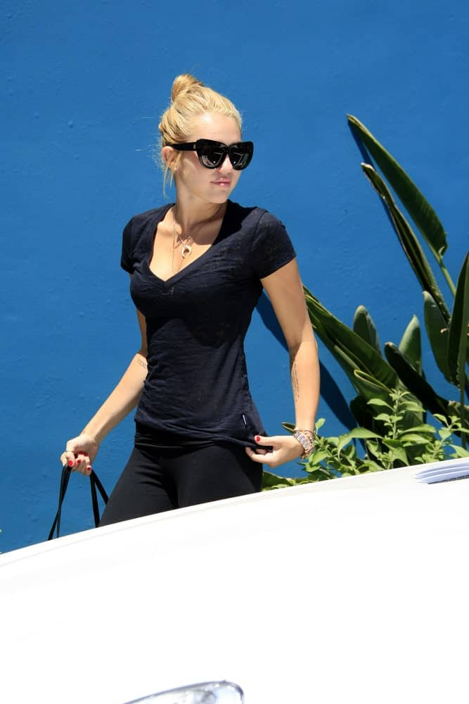Miley Cyrus was seen at a Pilates studio on July 16, 2012 in West Hollywood, California. She was wearing her yoga pants with her sandy blond hairstyle swept up to a high bun hairstyle with highlights.
