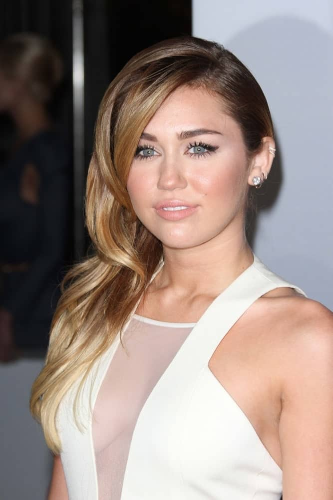 Miley Cyrus was at the 2012 People's Choice Awards Arrivals, Nokia Theatre in Los Angeles, CA on January 11, 2012. She wore a lovely white sheer dress that she topped with a classy side-swept wavy hairstyle with layers.