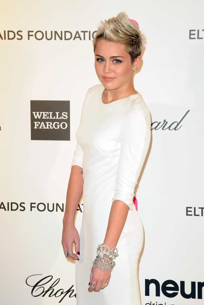 Miley Cyrus emphasized her lovely eyes with her white classy dress and highlighted spiky hairstyle when she arrived at the Elton John Aids Foundation 21st Academy Awards Viewing Party at the West Hollywood Park on February 24, 2013 in West Hollywood, CA.