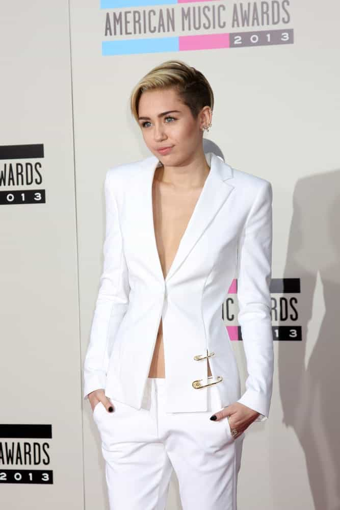 Miley Cyrus flashed a cute and sweet smile to go with her short undercut hairstyle and white androgynous outfit at the 2013 American Music Awards Arrivals at Nokia Theater on November 24, 2013 in Los Angeles, CA.