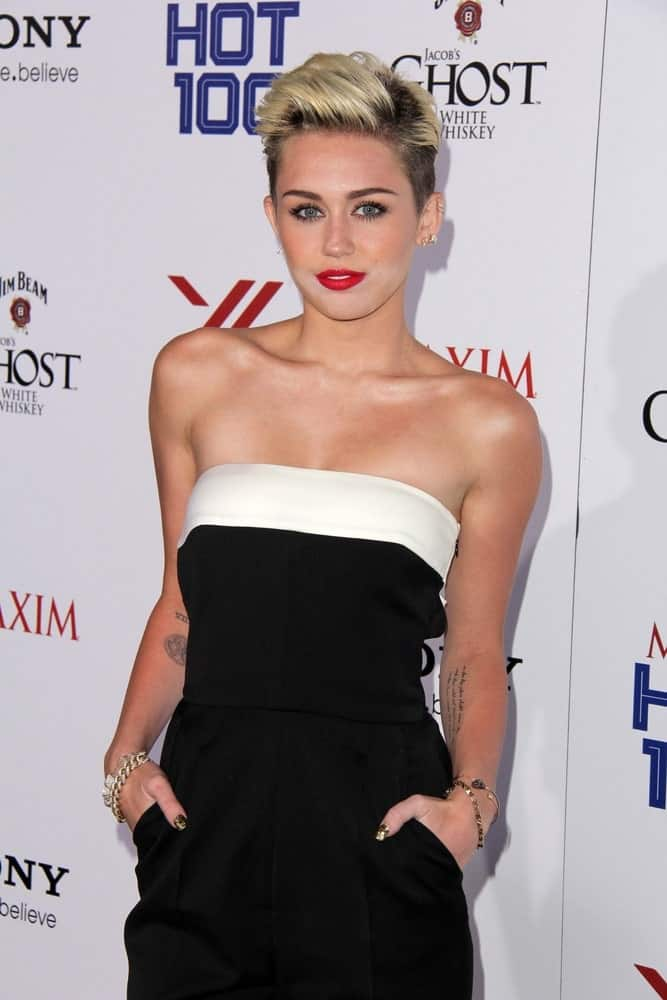 Miley Cyrus attended the 2013 Maxim Hot 100 Party held at the Vanguard in Hollywood on May 15, 2013. She looked stunning in her black and white romper, bold red lips and sexy side-parted and highlighted pixie fade hairstyle.