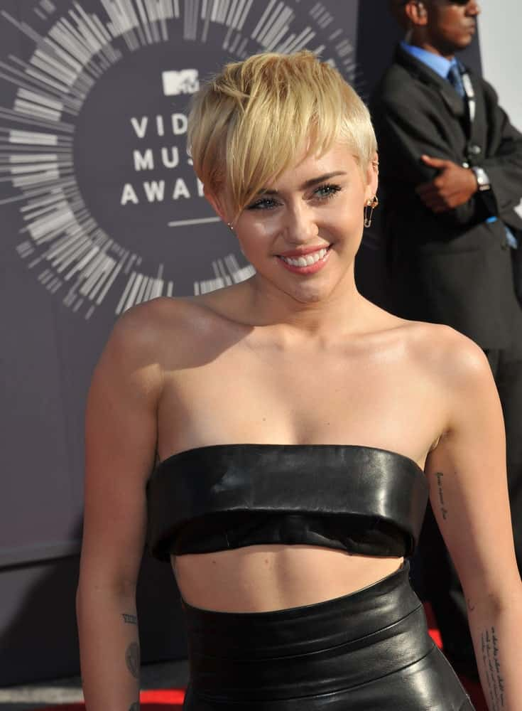 On August 24, 2014, Miley Cyrus attended the 2014 MTV Video Music Awards at the Forum, Los Angeles. She wore a sexy two piece black leather outfit that she paired with a sandy blond side-parted hairstyle.