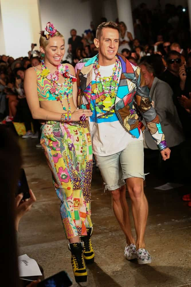 Miley Cyrus and designer Jeremy Scott walked the runway during MADE Fashion Week Spring 2015 at Milk Studios on September 10, 2014. Cyrus wore a colorful sexy outfit that went well with the headdress she wore on her side-swept pixie hairstyle.