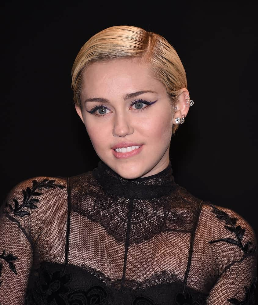 Miley Cyrus was quite classy in her vintage slick side-parted blond pixie hairstyle and sheer black dress at the Tom Ford Autumn/Winter 2015 Womenswear Collection Presentation on February 20, 2015 in Hollywood, CA.