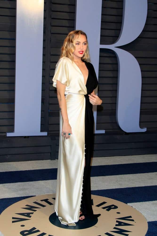 Miley Cyrus paired her black and white long dress with a loose and tousled wavy highlighted hairstyle and bold lips at the 24th Vanity Fair Oscar After-Party at the Wallis Annenberg Center for the Performing Arts on March 4, 2018 in Beverly Hills, CA.