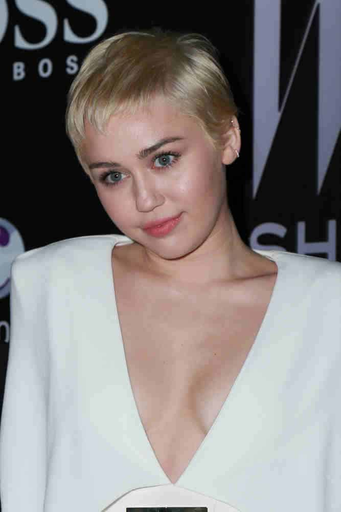 Miley Cyrus wears a fresh short haircut in a cute softly angled pixie style at the W Magazine`s Shooting Stars Exhibit on January 9, 2015.