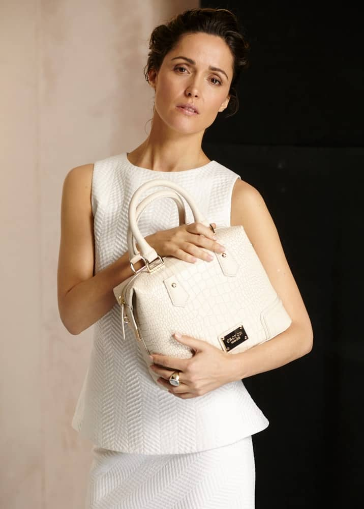 Actress Rose Byrne holding an Oroton bag on a photoshoot in London in 2015. She wore a white dress and her dark hair was styled into an elegant upstyle bun hairstyle.